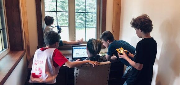 Mom tried to work at home computer with 4 young boys surrounding her
