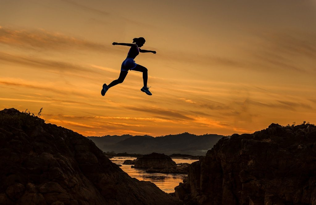 female athlete leaps over gorge at sunset