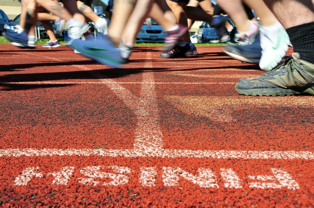 runners cross a finish line in a track meet